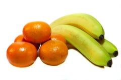 Mandarinas y plátanos en un fondo blanco Fotos de archivo