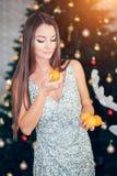 Mandarine douce de participation de jeune femme, humeur orange La fille dans une robe va manger des mandarines images stock