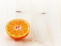 Mandarine halb auf Holztisch Lizenzfreies Stockfoto