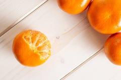 Mandarine with a leaf on grey wood. Group of three whole fresh orange mandarine one fruit is half peeled flatlay on white wood stock image