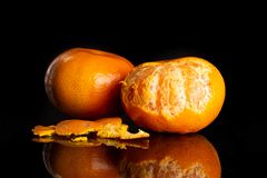 Mandarine with a leaf isolated on black glass. Group of two whole fresh orange mandarine rind pieces around one fruit is half peeled isolated on black glass royalty free stock images