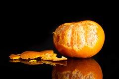 Mandarine with a leaf isolated on black glass. One whole fresh orange mandarine rind pieces around one fruit is half peeled isolated on black glass stock image