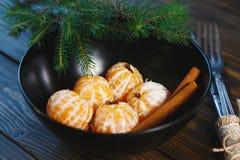 Mandarine mûre avec des feuilles, mandarine de mandarine dans la cuvette noire sur le fond en bois de table Mandarines d'agrumes  photographie stock libre de droits