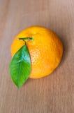 Mandarine mit dem Blatt getrennt auf hölzernem Hintergrund. Stockbilder