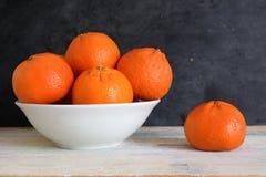 Mandarine och clementine bredvid en bunke på en vit trätabell Arkivbild