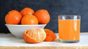 Mandarine- och clementinefruktsaft tjänade som bredvid en bunke på en vit trätabell Royaltyfri Fotografi