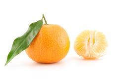 Mandarine oder Tangerine mit Blättern und abgezogenem Stockfoto