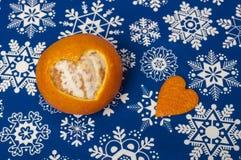 Mandarine orange juteuse avec la forme découpée en forme de coeur sur le papier d'emballage bleu avec des flocons de neige Images libres de droits