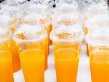 Mandarine ou jus de fruit smoothy colorée de mandarine en verre en plastique blanc image stock