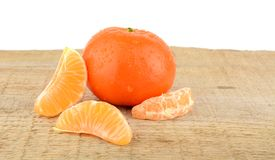 Mandarine with pieces  on wooden table Stock Images