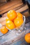 Mandarine. Some ripe fresh mandarins in dish on wooden background near the book Royalty Free Stock Photos
