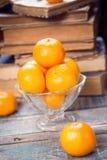 Mandarine. Some ripe fresh mandarins in dish on wooden background near the book Stock Photography