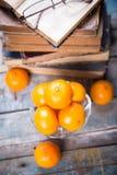 Mandarine. Some ripe fresh mandarins in dish on wooden background near the book Stock Images