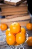 Mandarine. Some ripe fresh mandarins in dish on wooden background near the book Stock Photos
