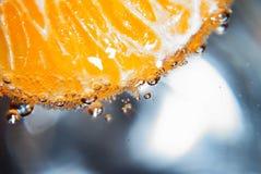 Mandarine sur la photo noire de fond en verre avec de l'eau images libres de droits