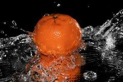Mandarine tombant dans l'eau sur le miroir noir photo stock