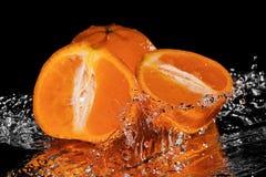 Mandarine tombant dans l'eau sur le miroir noir images libres de droits
