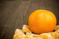 Mandarinen in der Schale und abgezogene Mandarinen auf dem Tisch Mandarinennahaufnahme Lizenzfreie Stockbilder