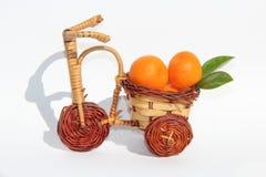 Mandarinen in einem Weidenfahrrad Stockbild