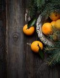 Mandarinen im Weinlesemetallvase auf einem hölzernen Hintergrund Stockfotos