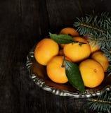 Mandarinen im Weinlesemetallvase und Niederlassungen der Kiefer auf einem hölzernen Hintergrund Stockbild