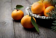 Mandarinen im Weinlesemetallvase und Niederlassungen von Kiefernnadeln auf einem hölzernen Hintergrund Stockfoto