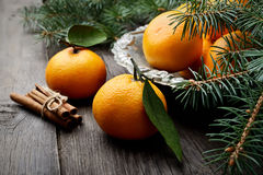 Mandarinen im Weinlesemetallvase und Niederlassungen von Kiefernnadeln auf einem hölzernen Hintergrund Stockfotografie