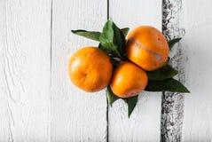 Mandarinen mit Blättern auf hölzernem Schreibtisch und Tuch Stockbild