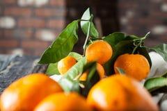 Mandarinen mit Blättern auf hölzernem Schreibtisch und Tuch Lizenzfreies Stockfoto