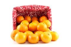 Mandarinen oder Tangerinen werden aus dem Korb heraus gegossen Lizenzfreie Stockfotografie