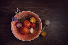 Mandarinen und Blumen liegen in einer Schüssel auf einer hölzernen braunen Tabelle als Nächstes Lizenzfreies Stockbild