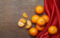 Mandarinen und roter Stoff Lizenzfreie Stockbilder