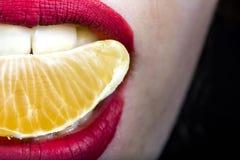Mandarinenscheibe im Mund in der Mädchenmundnahaufnahme lizenzfreie stockfotos