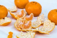 Mandarinenscheiben, Mandarinenhaut und ganze Mandarinen auf einem Weiß Lizenzfreies Stockbild