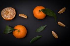 Mandarinenzitrusfrucht auf schwarzem Hintergrund Stockbilder