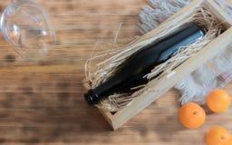 Mandarinenzusammensetzung, eine Flasche Champagner auf dem hölzernen Hintergrund Schein oben Kopieren Sie Platz lizenzfreie stockfotos