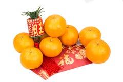Mandariner och röda paket med kinesisk characte för bra lycka Arkivfoton