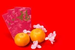 Mandariner och röda paket med kinesisk characte för bra lycka Royaltyfri Bild