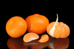 Mandarines. One of them peeled with one segment replaced by garlic clove, and two separate mandarin segments, on black reflecting surface Stock Images