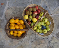 Mandarines and apples in a basket. View of some mandarines, apples and  kiwies in a basket on the stone floor Stock Photography