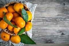 Mandarines avec des feuilles dans le panier sur le fond en bois rustique photographie stock libre de droits