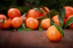 Mandarines avec des feuilles sur la surface en bois Photographie stock libre de droits