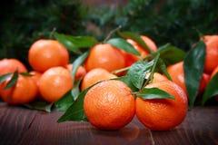Mandarines avec des feuilles sur la surface en bois Photo libre de droits
