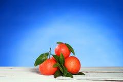 Mandarines avec des feuilles sur la surface en bois Photographie stock