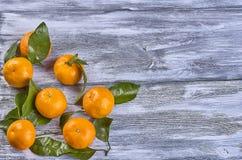 Mandarines avec des feuilles sur un fond en bois images stock