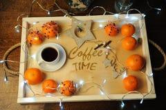 Mandarines, café, decoración y guirnalda en una bandeja de madera con grabado Imagen de archivo