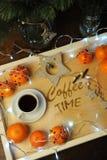 Mandarines, café, decoración y guirnalda en una bandeja de madera con grabado Imagen de archivo libre de regalías
