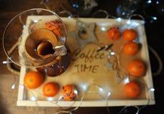 Mandarines, café, decoración y guirnalda en una bandeja de madera con grabado Imágenes de archivo libres de regalías