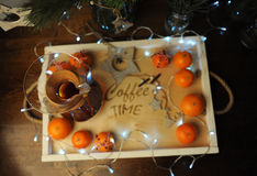 Mandarines, café, decoración y guirnalda en una bandeja de madera con grabado Foto de archivo libre de regalías