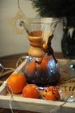 Mandarines, café, decoración y guirnalda en una bandeja de madera con grabado Fotos de archivo